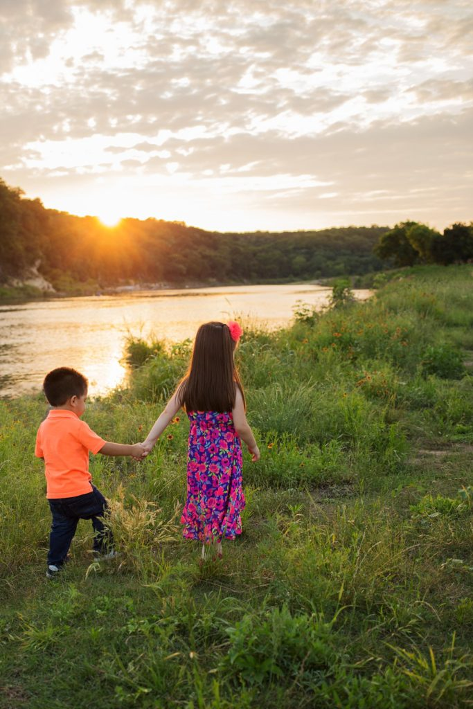 Sister and brother walking in sunset field | Austin San Antonio New Braunfels Family Photographer
